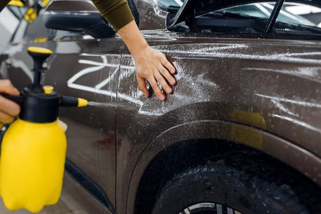 Перед нанесением защитной пленки рабочий-мужчина смачивает поверхность крыла автомобиля спреем. установка покрытия, защищающего краску автомобиля от царапин. новый автомобиль в гараже, детализация