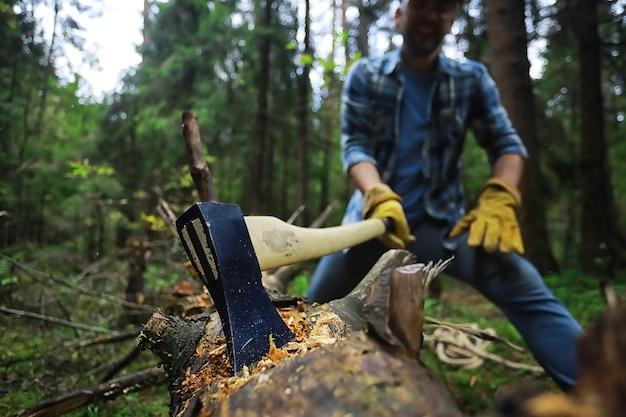 Рабочий-мужчина рубит дерево в лесу топором.