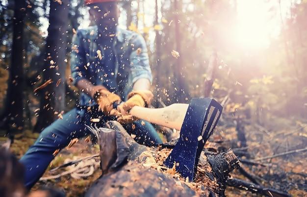 森で木を切り刻む斧を持つ男性労働者。
