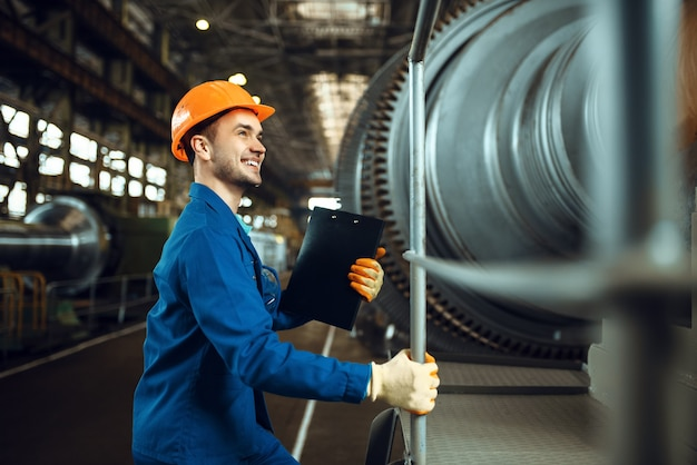Male worker with notebook, large turbine, plant. industrial production, metalwork engineering, machines manufacturing