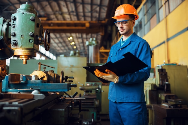 Male worker with notebook, lathe, plant. industrial production, metalwork engineering, power machines manufacturing