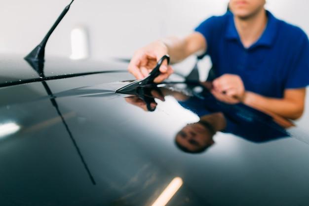 はさみ、車の着色フィルムのインストールプロセス、着色された自動ガラスのインストール手順を持つ男性労働者
