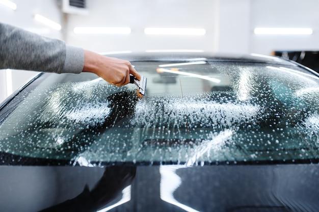 スキージを持った男性労働者は、色付け、チューニングサービスのために車を掃除します。ガレージの車の窓にビニールの色合いを塗る整備士、色付きの自動車ガラス