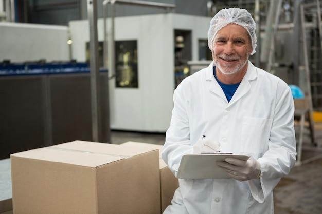 Lavoratore di sesso maschile che scrive sul blocco note nella fabbrica di bevande fredde