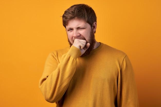 Мужчина-работник зевает, нуждается в отдыхе, не может проснуться рано утром, страдает бессонницей, чувствует себя слабым и усталым, изолирован на белом фоне