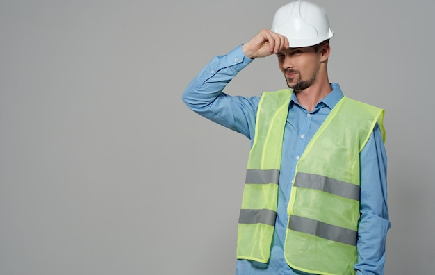 A male worker in a yellow vest and a white helmet on a gray background