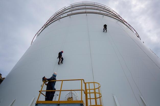 남성 작업자는 높이에서 두께 쉘 플레이트 저장 탱크 안전 작업의 로프 아래로 높이 탱크 로프 액세스 검사를 제어합니다.