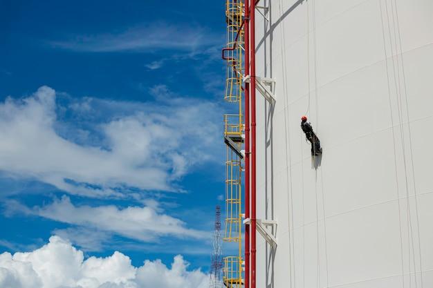 남성 노동자 제어 스윙 로프 아래로 높이 탱크 로프 두께 파이프 라인의 액세스 검사