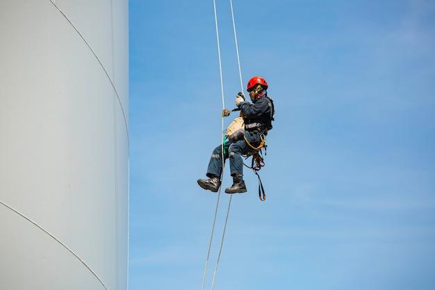 Рабочие-мужчины контролируют поворотный трос вниз по высоте резервуар веревочный доступ осмотр толщины оболочки резервуара для хранения газа безопасность работы на высоте