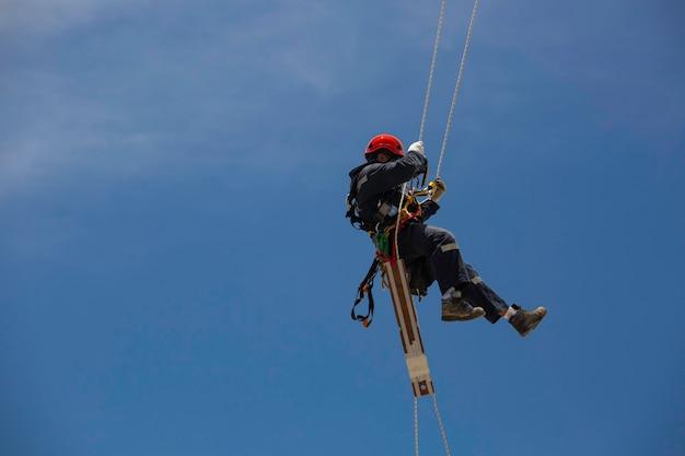 남성 노동자는 두께 쉘 플레이트 탱크 가스 배경 푸른 하늘의 높이 탱크 로프 액세스 검사를 아래로 스윙 로프를 제어합니다.