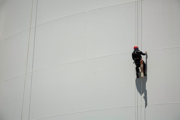 남성 근로자는 두께 탱크 가스의 높이 흰색 탱크 로프 검사를 아래로 스윙 로프를 제어합니다.
