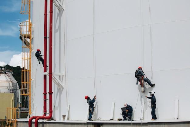 Мужчины-рабочие контролируют работу под веревкой вниз по высоте резервуара с веревочным доступом.