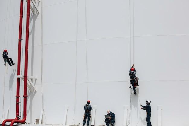 Рабочие-мужчины контролируют работу под веревкой вниз по высоте резервуара с веревочным доступом.
