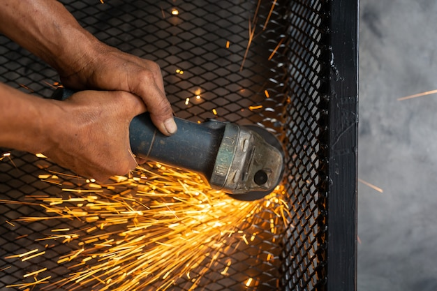 Male workers cut and weld metal with spark.