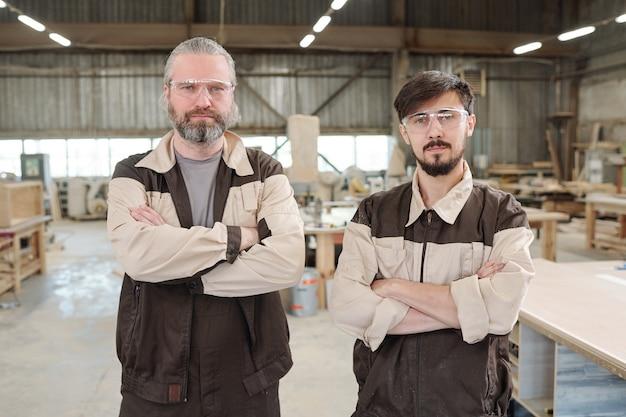 Рабочие-мужчины в спецодежде и защитных очках, использующие шлифовальный станок для обработки поверхности деревянной доски на верстаке