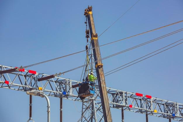男性労働者クレーンへの高圧送電電柱の設置は高所作業のリスクがあります