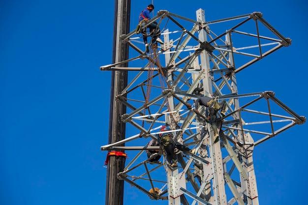 男性労働者高圧送電電柱の設置は、高さのリスクがあるオンラインの柱の鉄骨工事