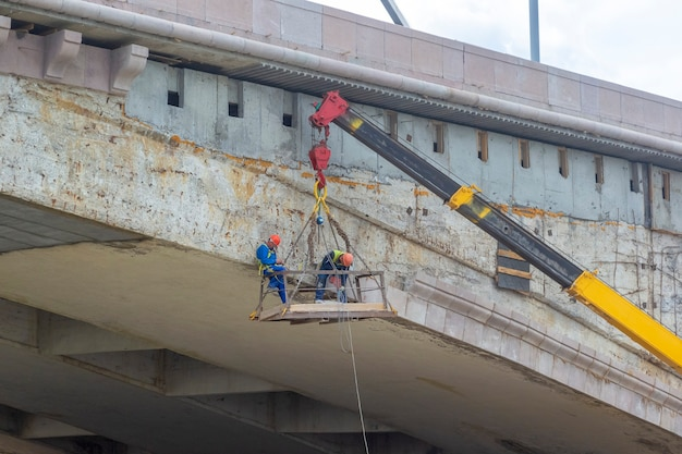 Рабочие-мужчины ремонтируют мост