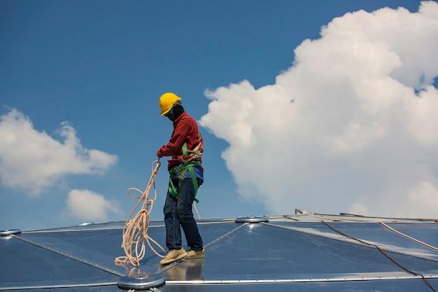 Безопасность высоты веревочного доступа мужчин рабочих, соединяющаяся с ремнями безопасности с восемью узлами
