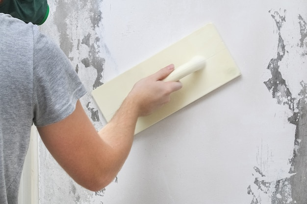 Male working polishes grinds wall. plastering float trowel.