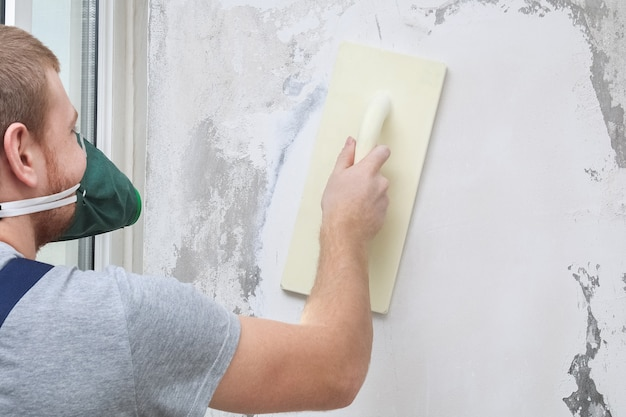 Male working polishes grinds wall