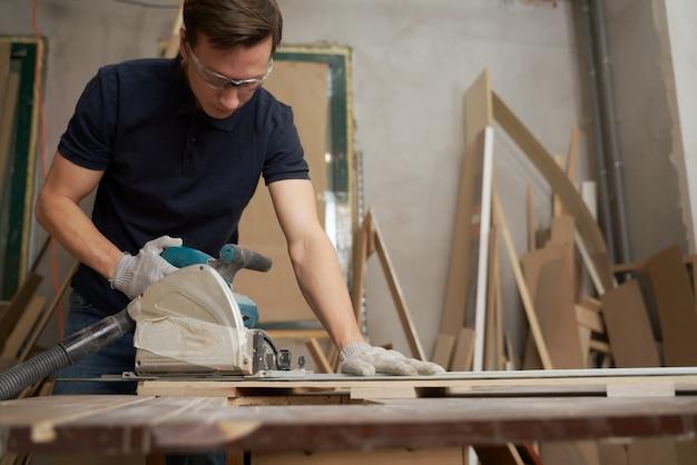 Мужчина работает над лобзиком в мастерской