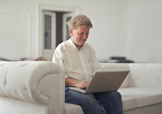 男性は自宅でラップトップを使用しています
