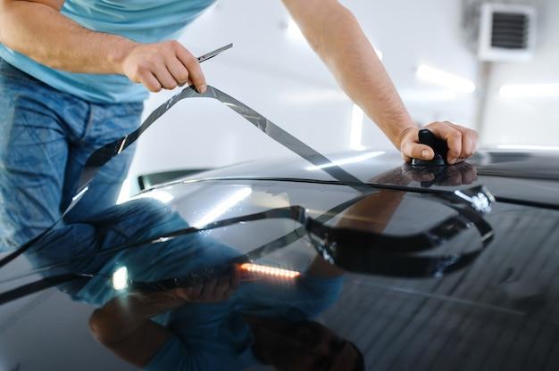 男性のラッパーは車の色合い、チューニングサービスをカットします。ガレージの車の窓にビニールの色合いを塗る労働者、色付きの自動車ガラス