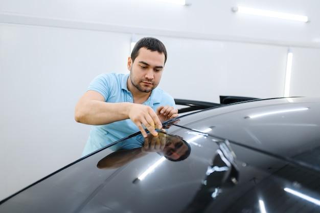 男性のラッパーは車の色合い、チューニングサービスをカットします。ガレージの車の窓にビニールの色合いを塗る労働者