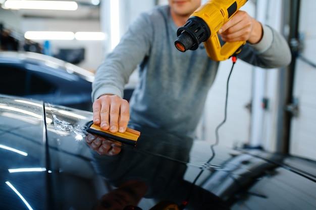 男性のラッパーはスキージとヒートガン、車の着色サービスを保持します。ガレージの車の窓にビニールの色合いを塗る労働者、色付きの自動車ガラス
