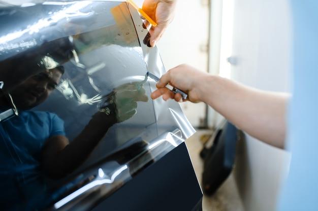 男性のラッパーは、日焼け止めフィルム、車の着色サービスを保持しています。ガレージの車の窓にビニールの色合いを塗る労働者、色付きの自動車ガラス