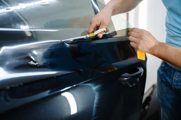 男性のラッパーは、日焼け止めフィルム、車の着色サービスを保持しています。ガレージの車の窓にビニールの色合いを適用する労働者