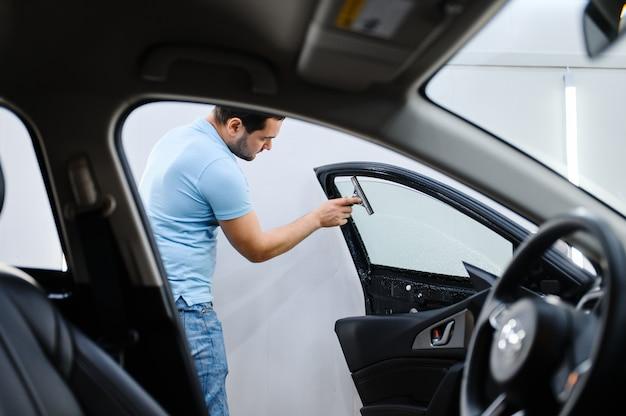 男性のラッパーは、車の色合い、チューニングサービスをインストールします。ガレージの車の窓にビニールの色合いを塗る労働者、色付きの自動車ガラス