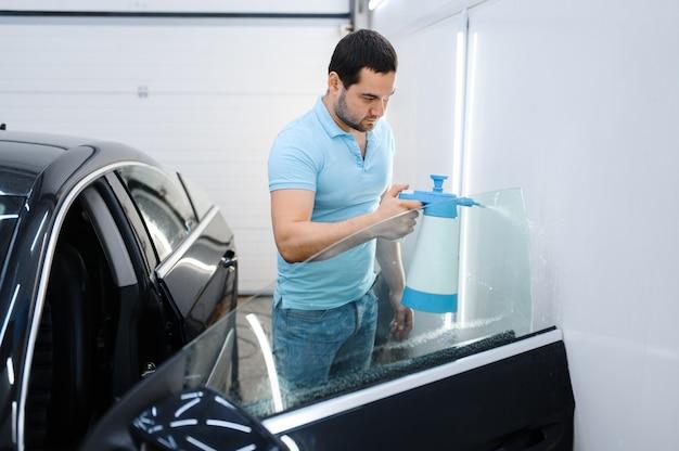 スプレー付きの男性ラッパーは、車の着色、チューニングサービスの準備をします。ガレージの車の窓にビニールの色合いを塗る労働者、色付きの自動車ガラス