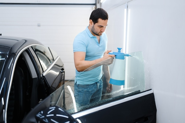 Male wrapper with spray prepares car for tinting, tuning service. worker applying vinyl tint on vehicle window in garage, tinted automobile glass