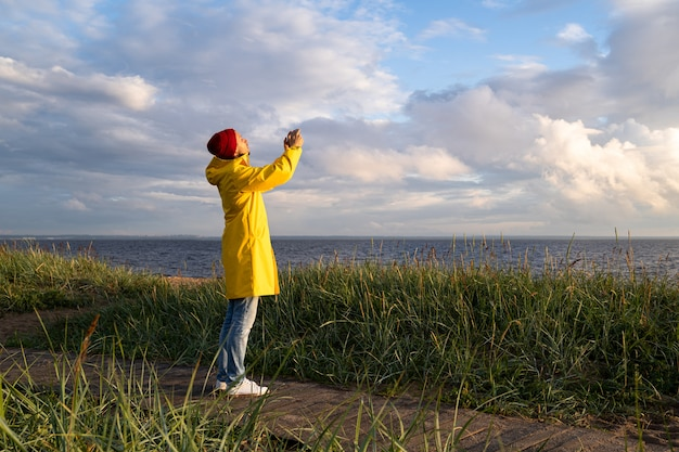Male in yellow raincoat wear red hat standing on the beach and takes photo on smartphone