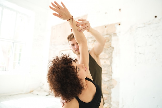 Male yoga instructor helping afro american woman
