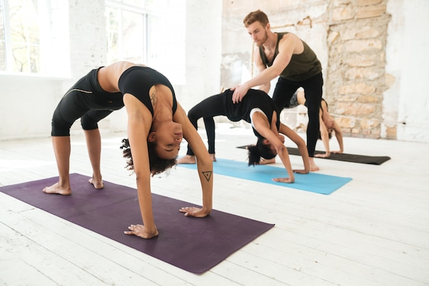 Male yoga trainer helping a woman to do yoga stretches