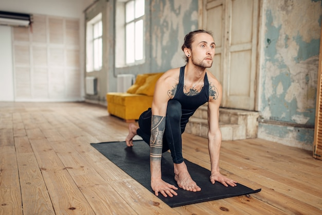 Male yoga with tattoo on hand doing exercise