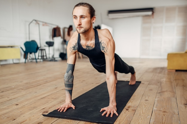 Male yoga with tattoo on hand doing push up exercise in gym with grunge interior. fitness workout indoors
