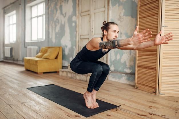 グランジインテリアのジムでマットの上でバランス運動をしている手に入れ墨の男性ヨガ。屋内でのトレーニングに適合