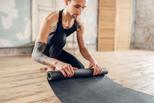 Мужская йога с татуировкой на руке готовит коврик для тренировки в тренажерном зале с интерьером в стиле гранж.