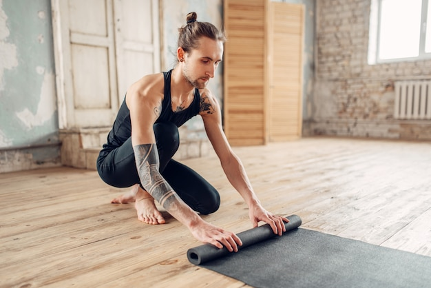 Мужская йога с татуировкой готовит коврик для тренировки