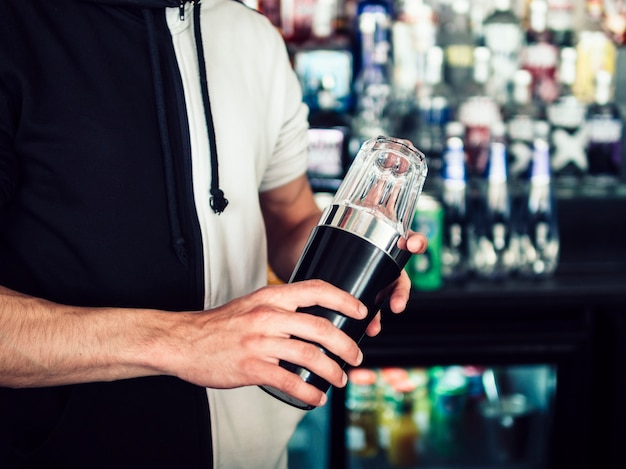 Male young bartender using tumbler to make drink