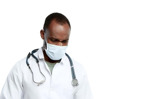 聴診器と白い壁に分離されたフェイスマスクを持つ男性の若い医者