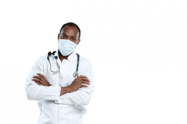 白で隔離される聴診器とフェイスマスクを持つ男性の若い医者