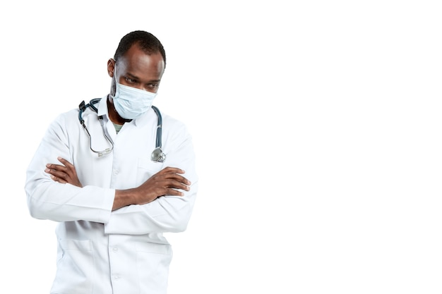 Male young doctor with stethoscope and face mask isolated on white  wall