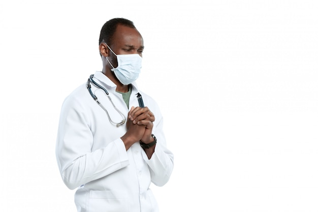 Male young doctor with stethoscope and face mask isolated on white