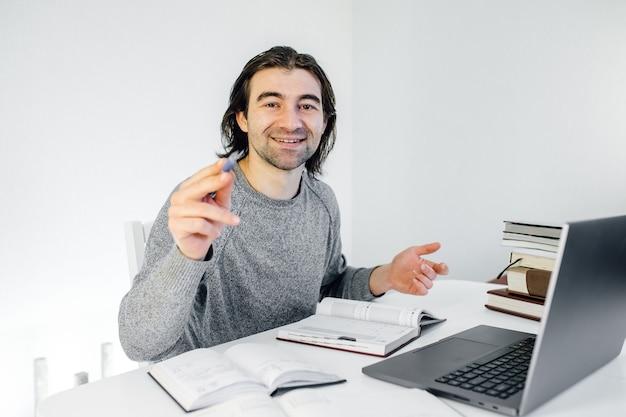 Male young hispanic school math teacher looking at webcam