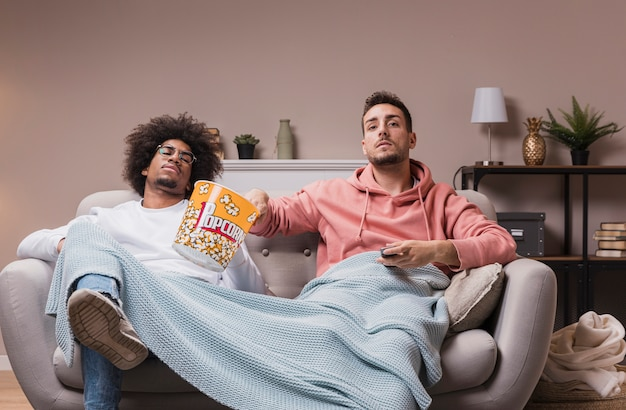 Males eating popcorn and watching movie